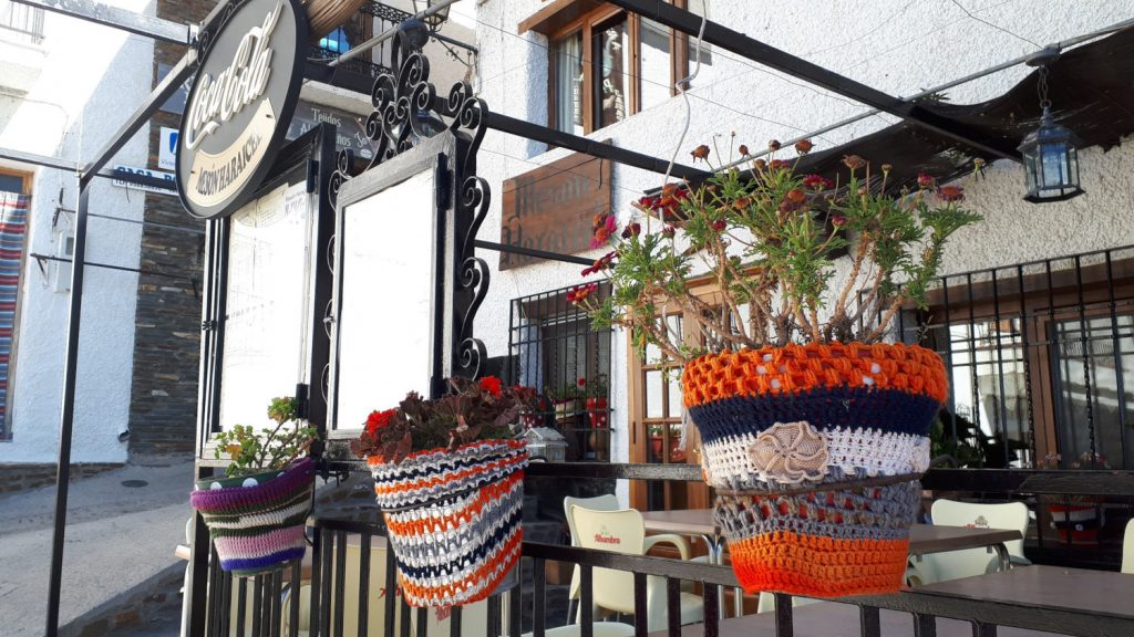 Small cafe in Trevelez with flowerpots in knitted jumpers!