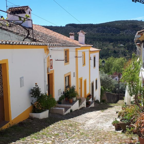 Whitewashed and yellow striped house on a cobbled lane