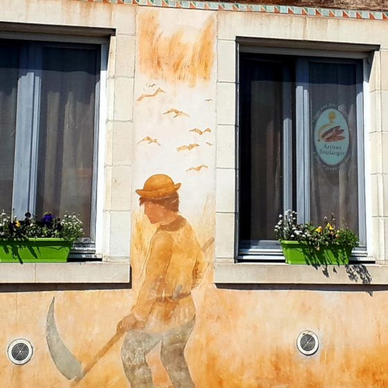 Artwork on a building in St Savin showing the local farming activities