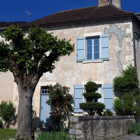 A beautiful stone house with pretty blue shutters