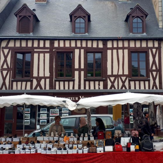 Market stalls in front of traditional half-timbered building