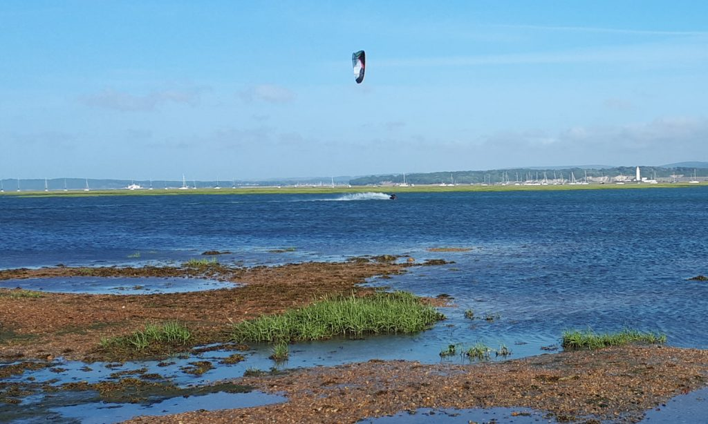A kitesurfer making the most of the windy weather at Keyhaven Marshes