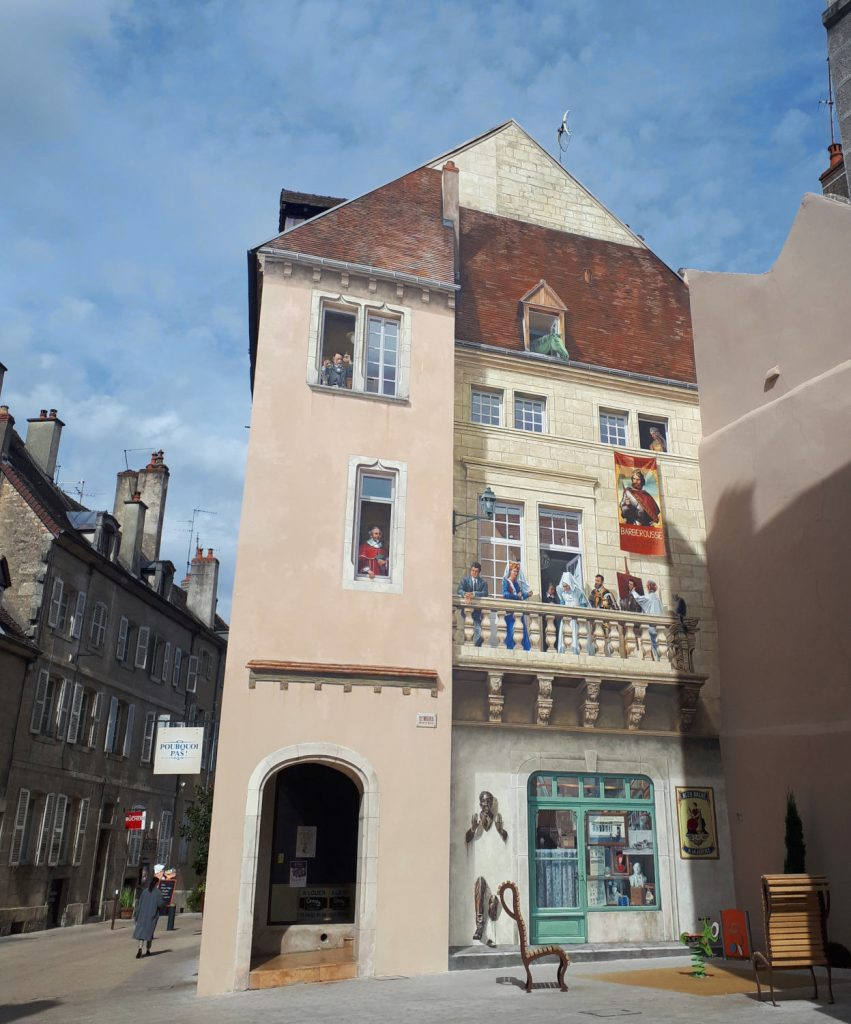 A painted building in Dole with Louis Pasteur in the top window